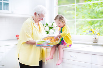 Beautiful grandmother, little girl cooking pie in white kitchen