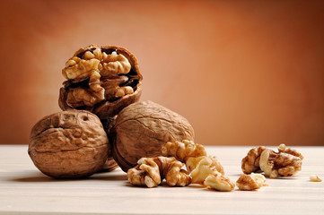 group of walnuts on a table with brown background