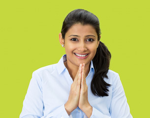 Namaste. Smiling young woman on green background