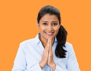 Namaste. Smiling young woman on orange background