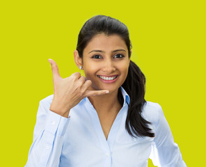 Young businesswoman giving call me gesture, green background