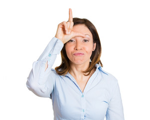 Portrait angry middle aged woman giving loser sign, gesture