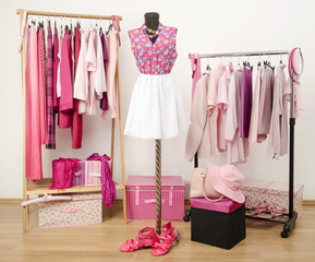 Wardrobe with all shades of pink clothes, shoes and accessories.