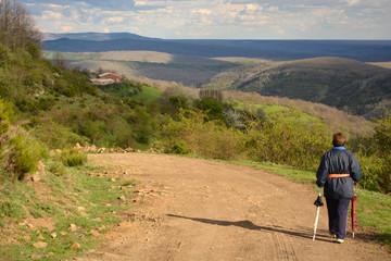 mujer mayor caminando por un camino de montaña