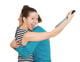 Back stabber woman hugging lady, at same time trying to stab her