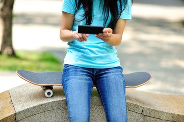 skateboarding woman use her cellphone at  skateboard park