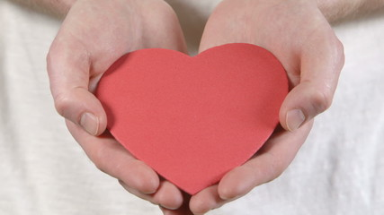 A man holds a heart in his hands, offering it forward.