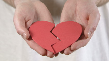 A man holds a broken heart in his hands