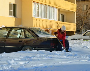 Girl digs car out of the snow