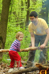 Daddy little girl helps to kindle a fire in the forest