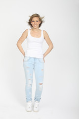Girl in blue jeans, white shirt and white sport shoes posing