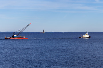 Portland, Maine - Tugboat towing crane in front of lighthouse