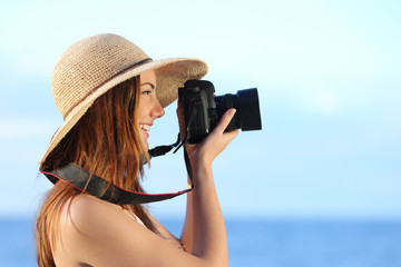 Happy woman on vacation photographing with a dslr camera