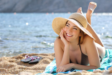 Happy woman thinking and looking at side lying on the beach