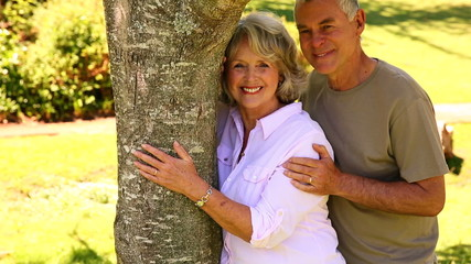 Retired couple leaning against tree smiling at camera