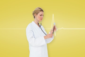 Composite image of blonde doctor listening with stethoscope