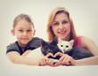 two girls hugging cats