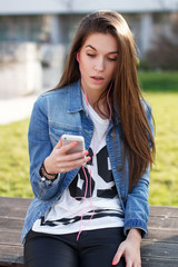 Young woman holding smartphone, reading news