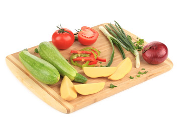 Composition of vegetables on wooden platter.