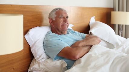 Senior man lying in bed thinking