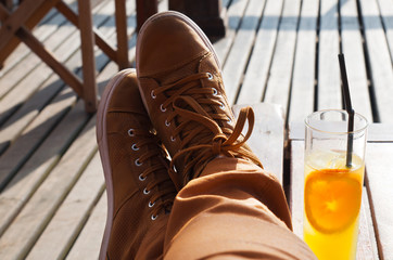 Foot on the table in a  bar outdoor. Resting with a refreshment