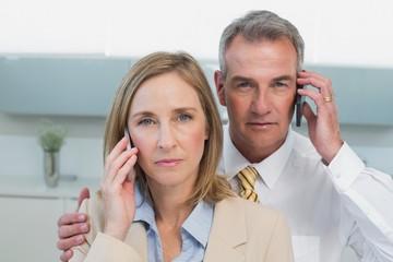 Portrait of a business couple using cellphones