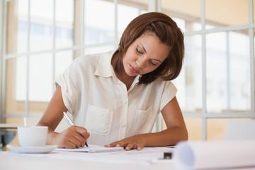 Businesswoman working on blueprint in office