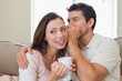 Man whispering secret into a happy womans ear in living room