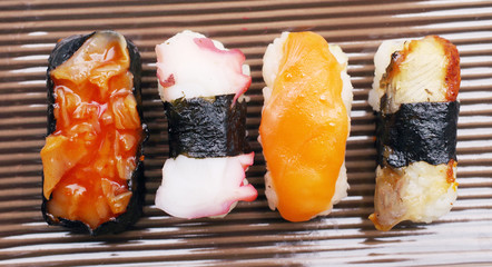 Sushi nigiri in with dish with bamboo sticks