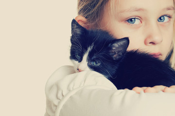 girl hugging kitten