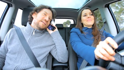 Couple in love driving in vacation talking on the phone