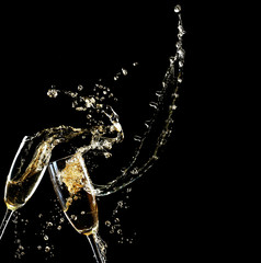 Glasses of champagne with splash, on black background