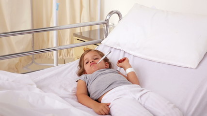 Little girl lying in hospital bed using a tablet