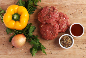 Raw beef patties with vegetables, barbecue sauce and spices