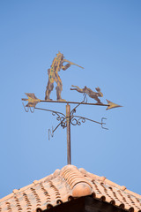 A metal chaser and rabbit weather vane on a roof.