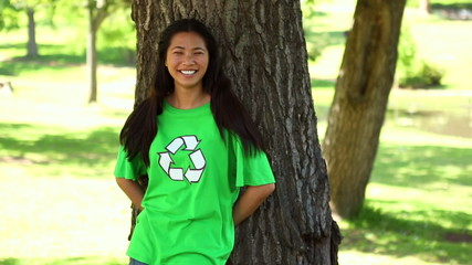 Happy environmental activist leaning against a tree
