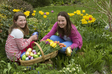 Easter egg hunt girls with chocolate eggs and Spring flowers