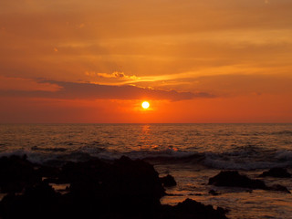 Sunset over ocean with lava rocks of Holoholokai Beach in the fo
