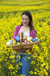 Girl with Easter eggs in a trug with backdrop of rapeseed field