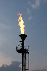 Oil burning torch against sunset sky