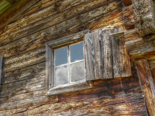 Fenster in der Holzwand einer Almhütte in HDR