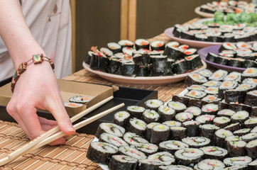 young woman holding sushi in sushi bar