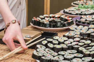 young woman holding sushi in sushi bar