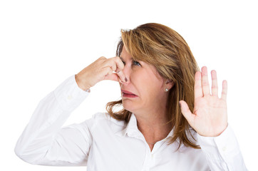 Something stinks, woman pinches her nose, disgust on face