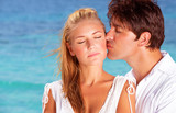 Happy couple kisses on the beach