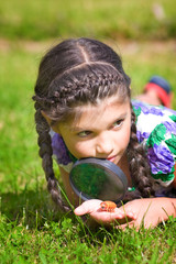 Smiling girl with magnifying glass and beetle