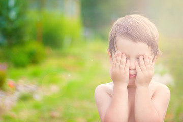 little child is playing hide-and-seek hiding face