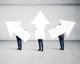 three men holding white arrows