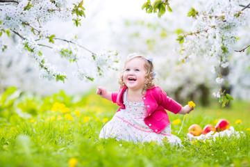 Beautiful toddler girl eating apple in blooming garden