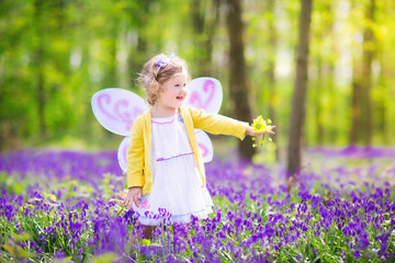 Adoable toddler girl in fairy costume in bluebell forest